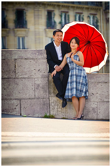 embracing couple with red umbrella in paris