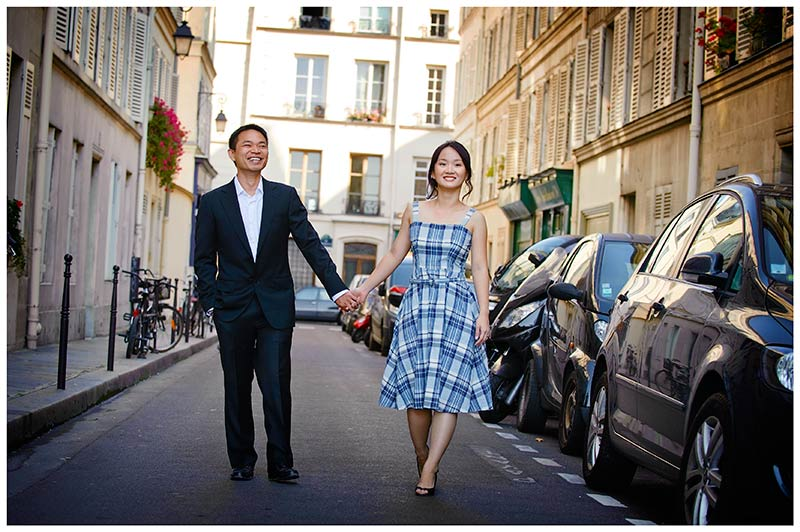 Smiling couple waliking hand in hand through streets of Paris