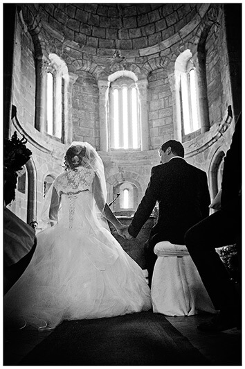 italian wedding couple holding hands at the church alter