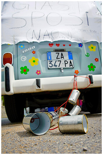 na italian vw van is decorated with tin cans for a wedding