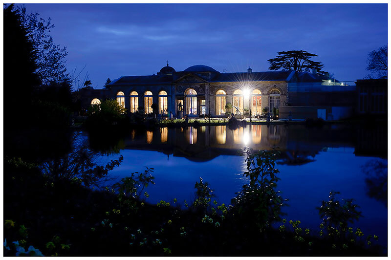 woburn sculpture gallery under a blue night sky viewed across the lake