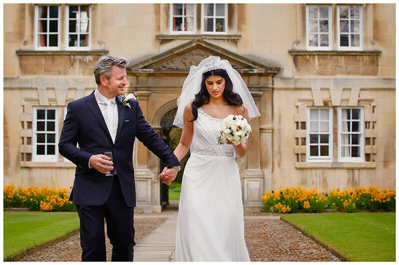 bride groom walking holding hands christs college cambridge
