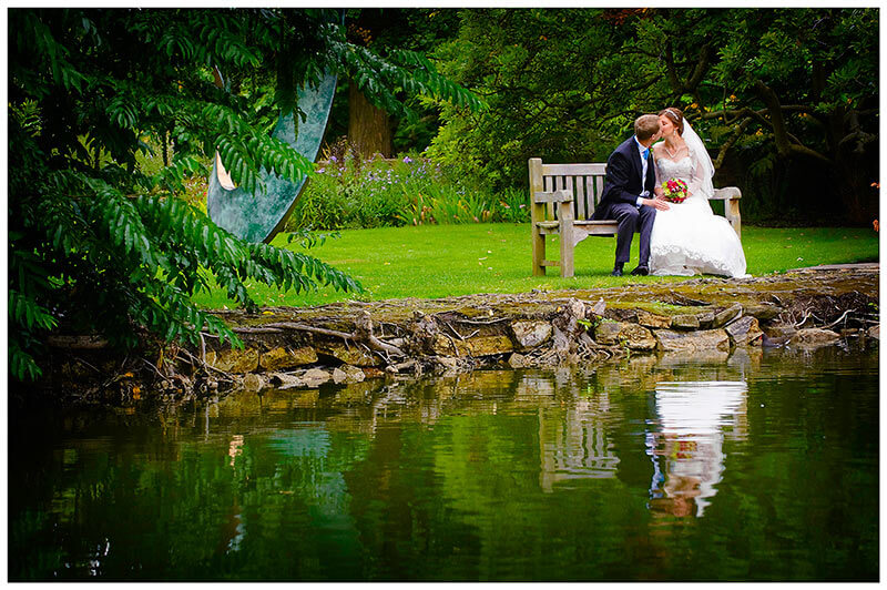 bride groom sitting on bench near water kiss