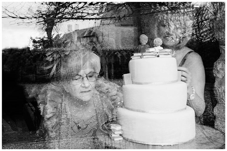 Tythe Barn Bicester Wedding grandmother looking at wedding cake