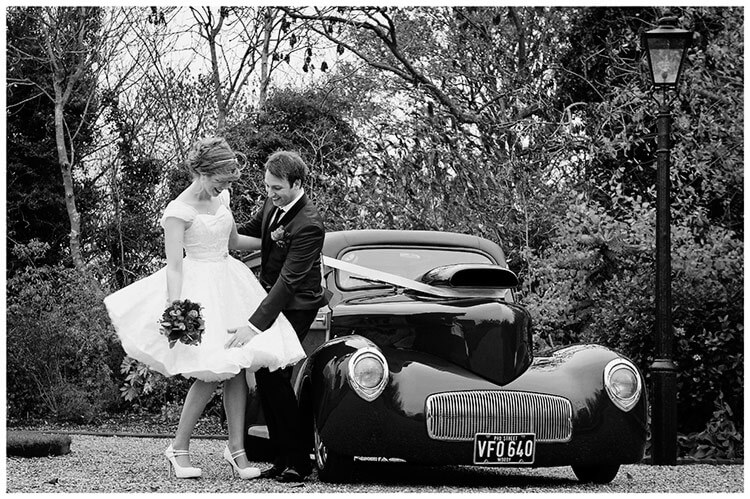 Tythe Barn Bicester Wedding groom holds brides dress to stop it blowing in wind