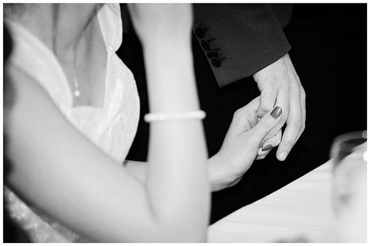 Tythe Barn Bicester Wedding bride holds grooms hand during speech