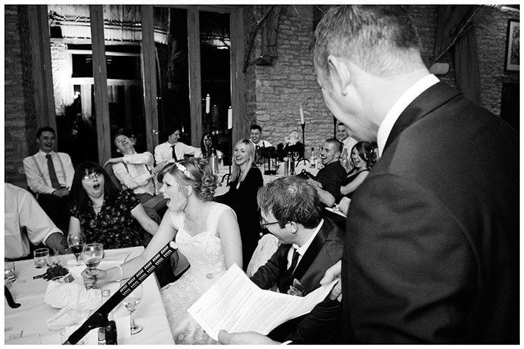 Tythe Barn Bicester Wedding brides shocked face during bestman speech