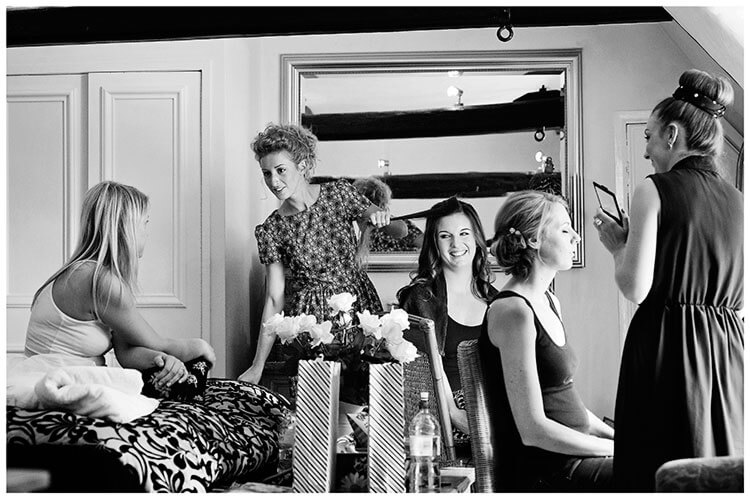 brides maids getting hair done bride sitting on bed