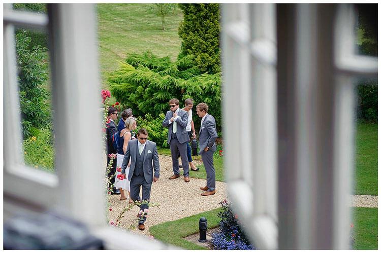 groom ushers viewed through window