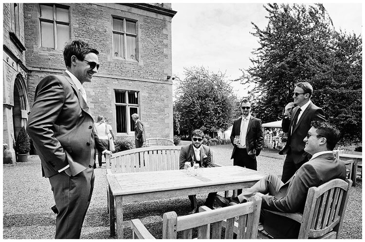 groom talking to guests outside wadenhoe house wedding venue
