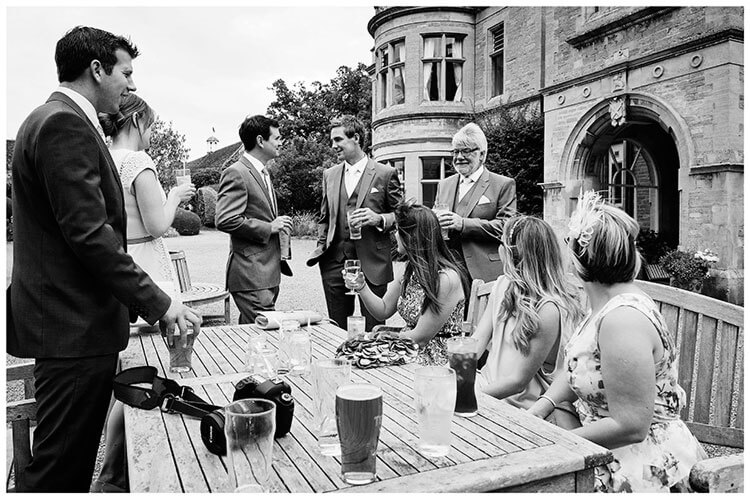 guests groom having drink outside wadenhoe house wedding venue