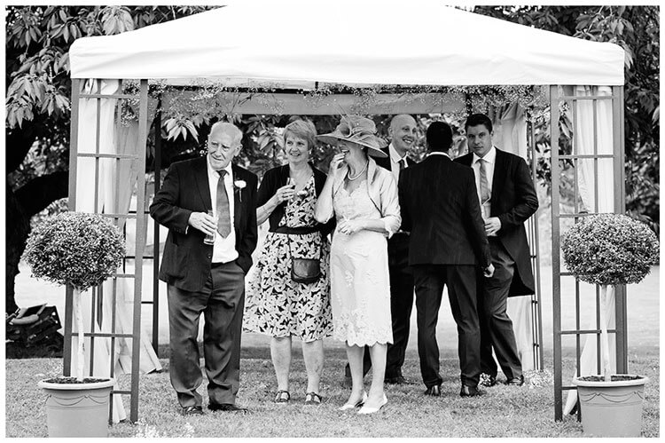 guests standing under marquee out of rain