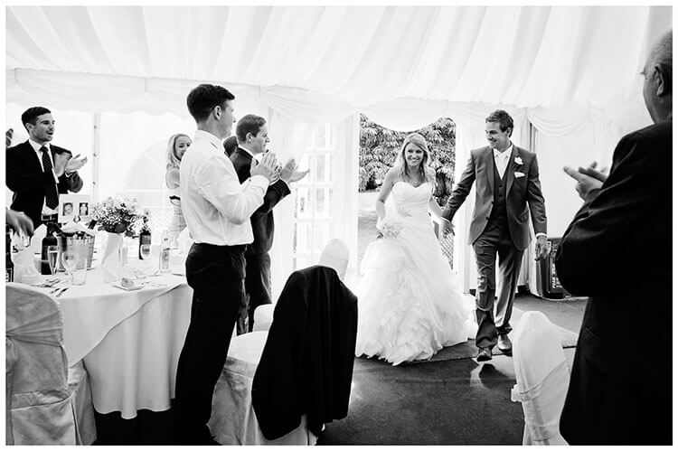 bride groom holding hands enter wedding marquee
