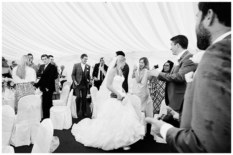 bride groom walking through marquee greeted by wedding guests
