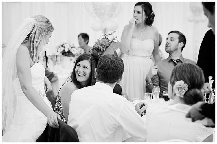 bride talking wedding guests sat dining table