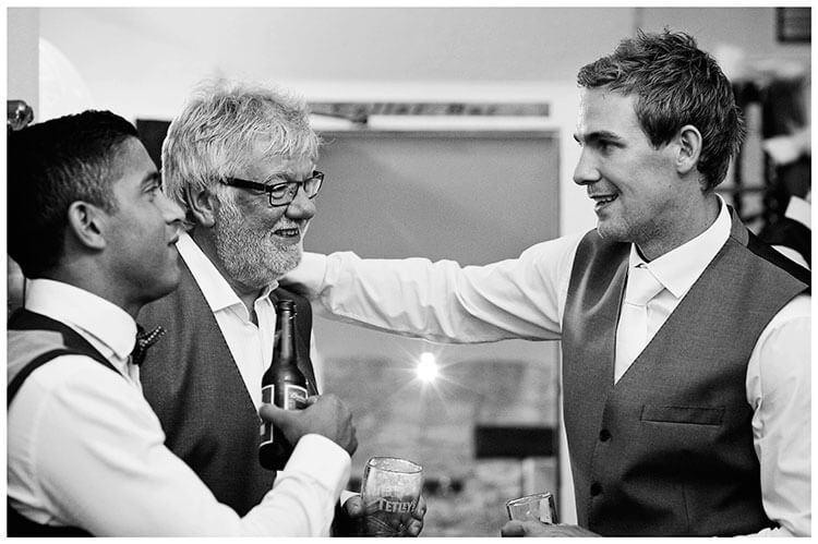 groom arm on father talking to friend