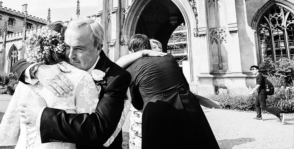 Bride & Groom getting hugs from Parents outside st Johns College Cambridge by Documentary Wedding Photographer Scott-Wood Photography