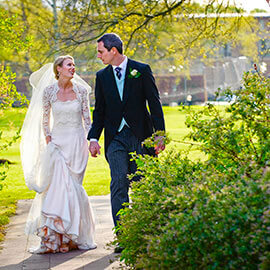 homerton college wedding smiling bride groom walk holding hands looking at each other