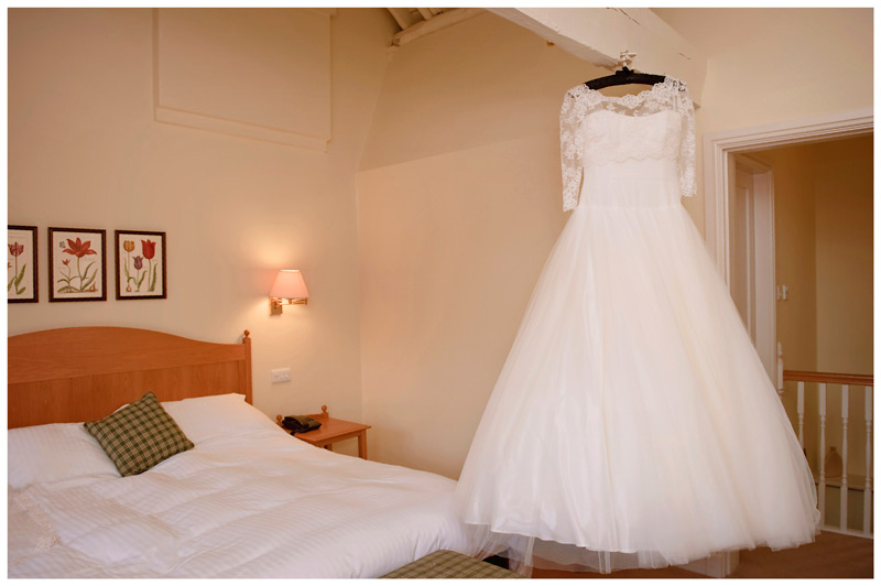 wedding dress hung from bedroom beams