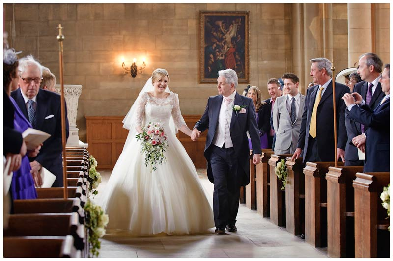 woburn abbey wedding smiling bride walking down aisle with father