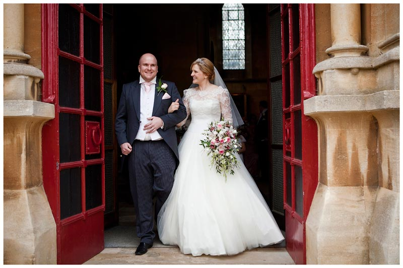 smiling bride and groom leaving Woburn Abbey after ceremony