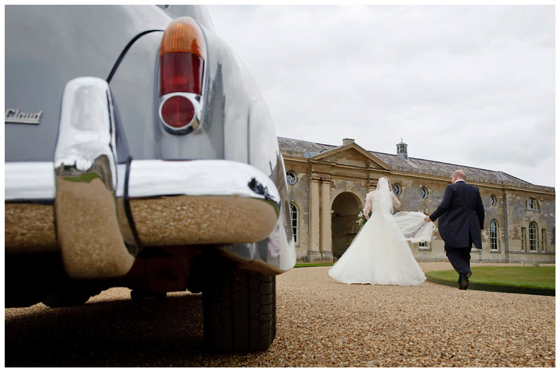 woburn sculpture gallery wedding groom hold brides veil as they walk away from car