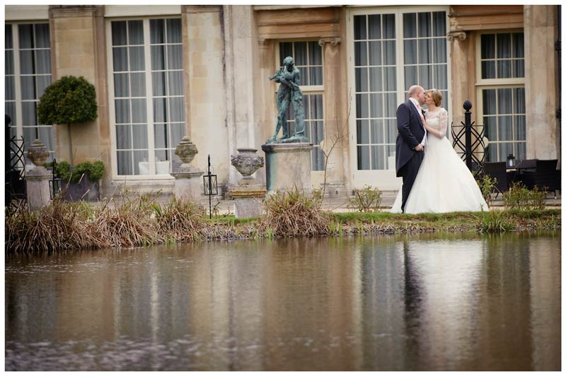 bride kisses her groom nest to water with woburn sculpture gallery in background