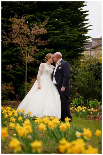 woburn sculpture gallery gardens full of romantic daffodils bride groom kissing in background