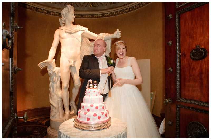 woburn sculpture gallery wedding groom pulls face bride laughs about to cut cake