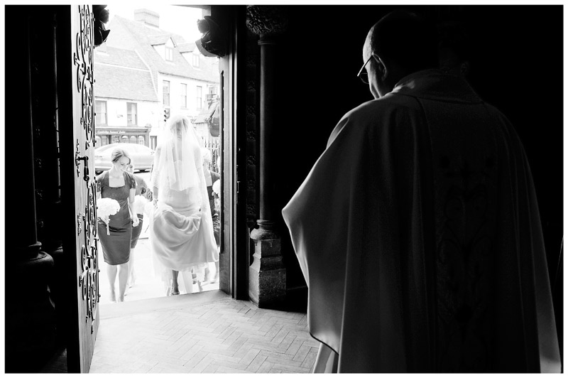 bride enters OLEM Church Cambridge watched by vicar