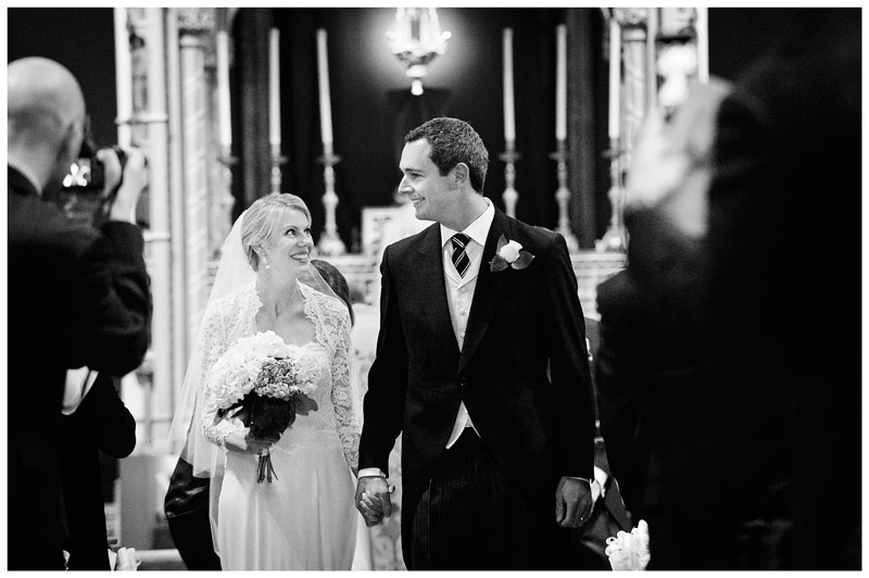 bride smiles at groom as they walk down aisle of OLEM Church in Cambridge