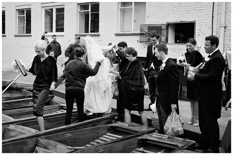 Homerton College Wedding helping bride get on punt