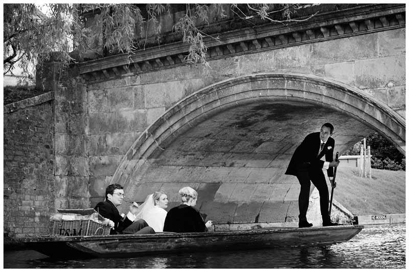 Wedding party pass under bridge whilst riding on punt