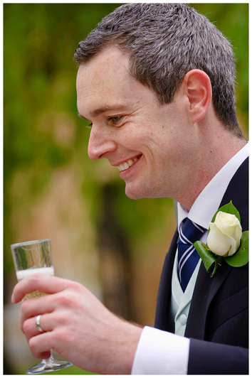 groom unposed portrait holding champagne glass