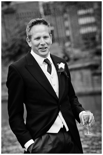 man in morning suit holding champagne glass