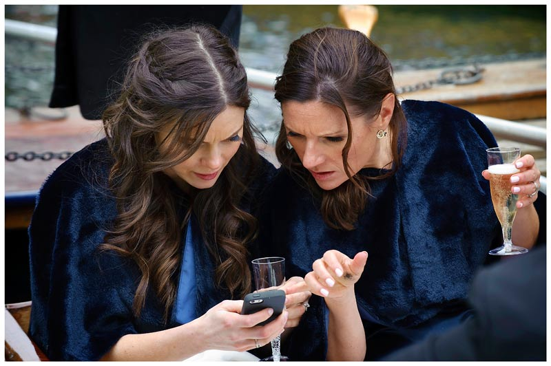 bridesmaids looking at phone whilst sitting on punt