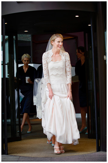 smiling bride lifting dress as she walks