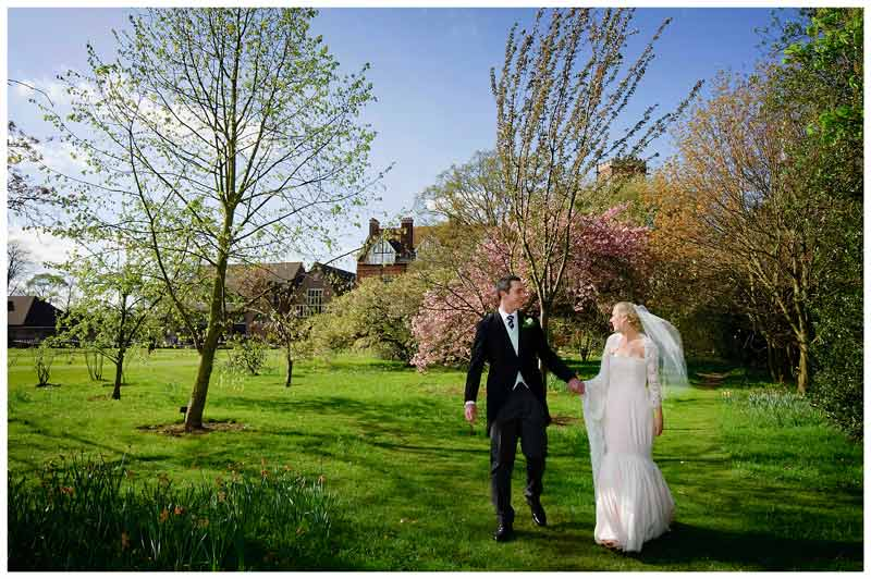 bride groom walking amoungst trees in grounds of Homerton College