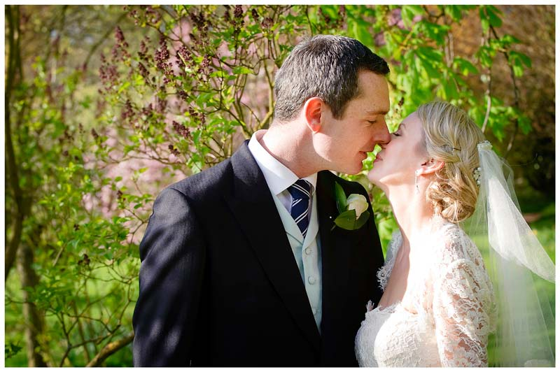 bride kisses groom in grounds of Homerton College