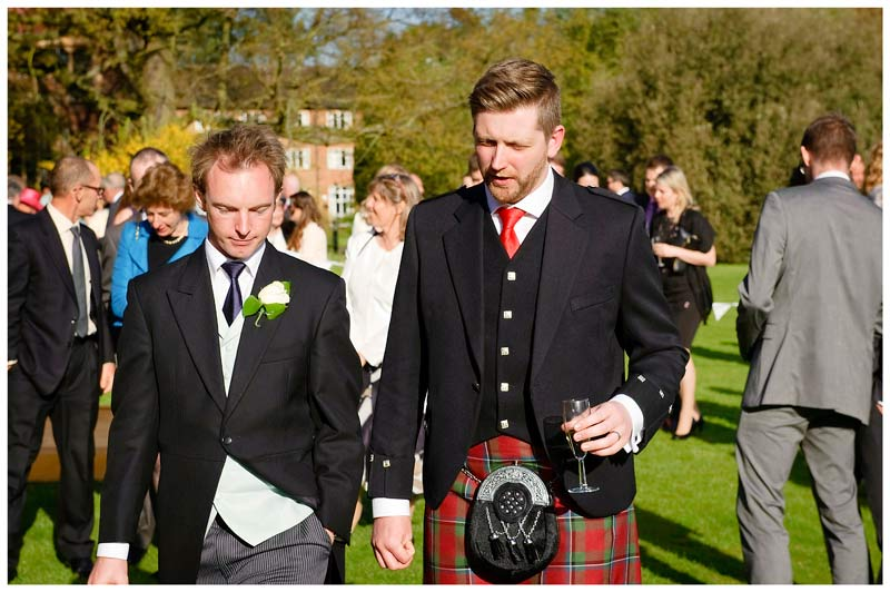 Wedding guest in kilt talks to guest as walking