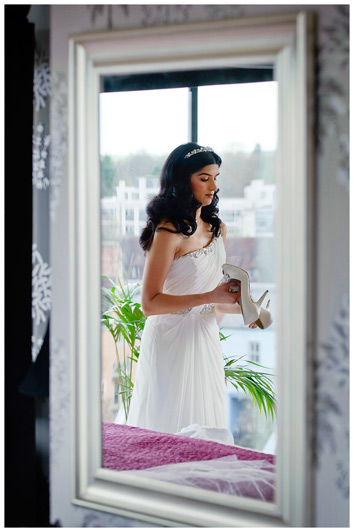 bride in mirror holding shoes