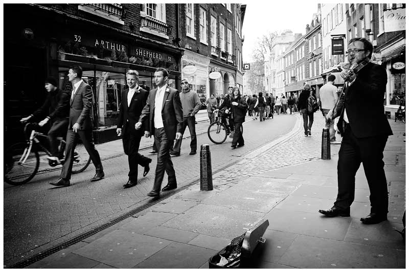 grooms men walking past violinist in street