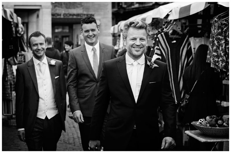 smiling grooms men walking through market