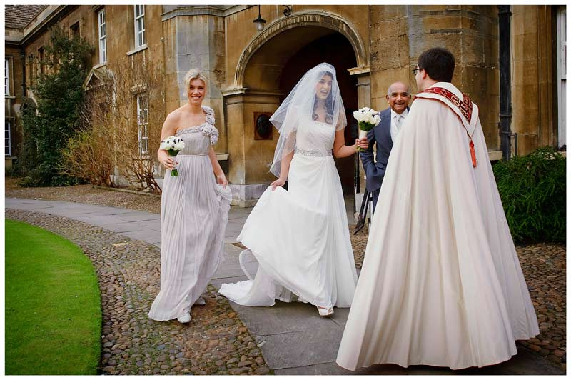 vicar greets bridal party in court of Christs College Cambridge