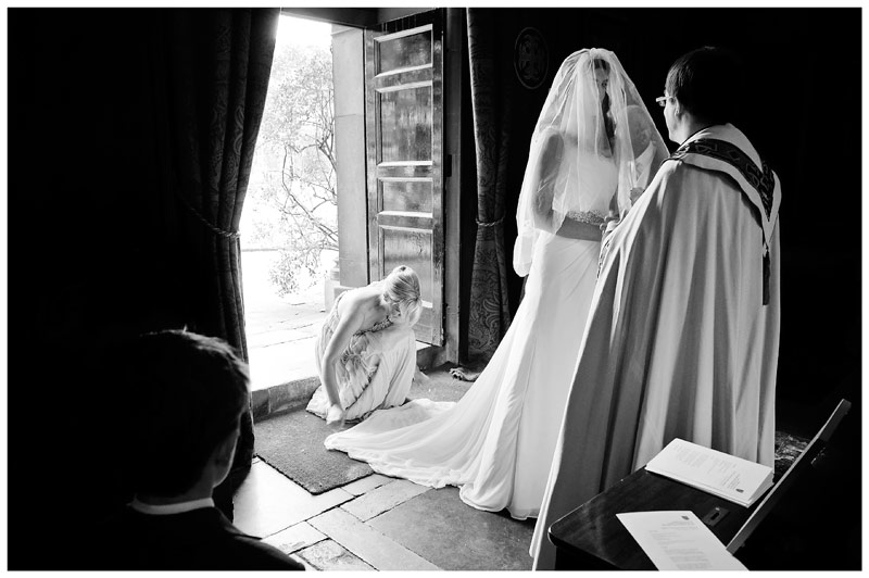 bride greeted by vicar in chapel of Christs College Cambridge bridesmaid adjusts brides dress little boy watches