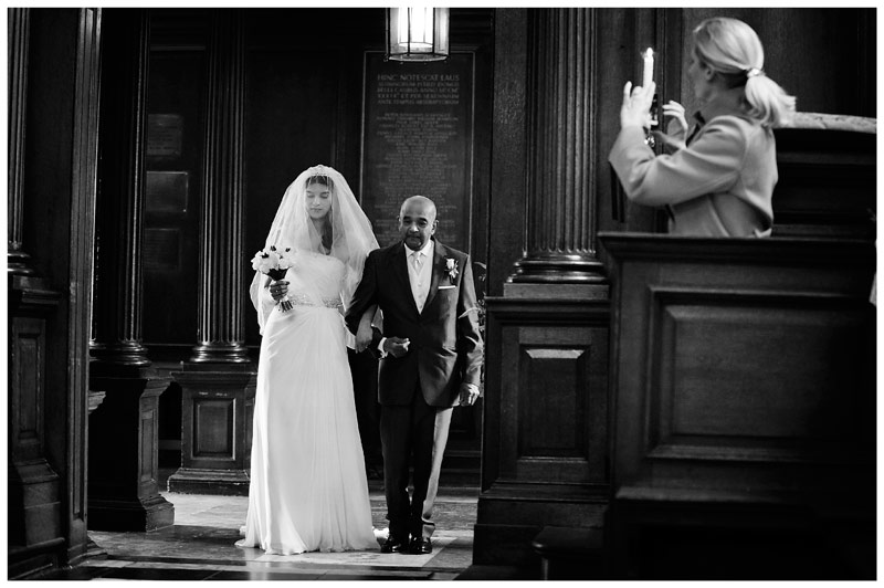 bride enters Chapel at Christs College Cambridge whilst guest takes photo