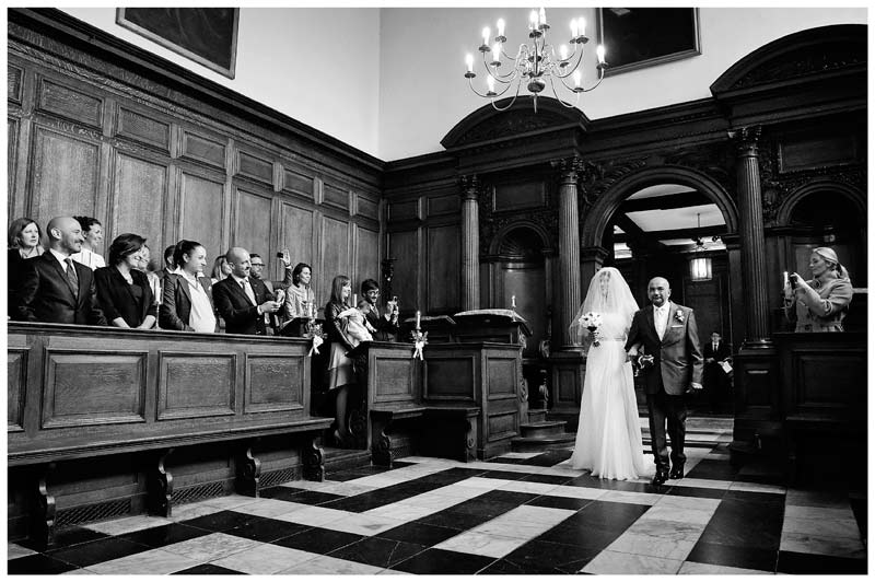 bride enters Christs College Cambridge chapel watched by guests