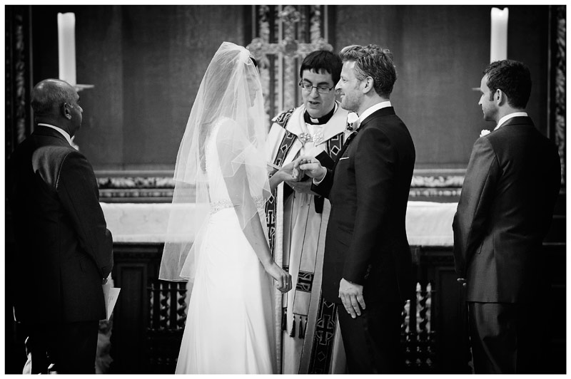 bride and groom face each other at alter holding hands in Christs College Cambridge  chapel