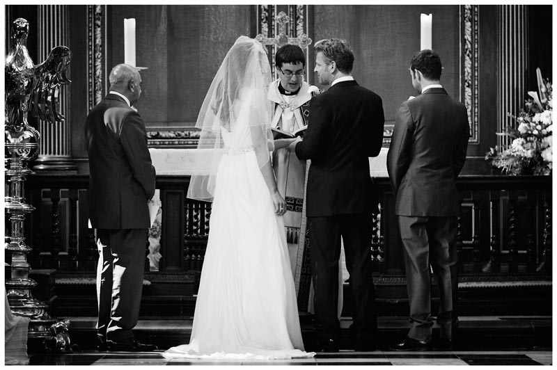 groom places ring on brides finger in Christs College Cambridge chapel