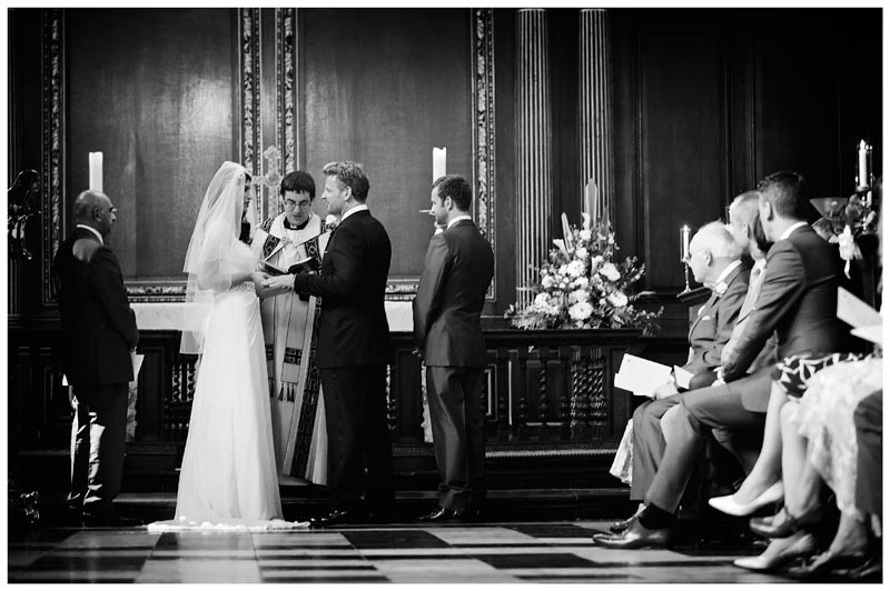 bride places ring on grooms finger in Christs College Cambridge chapel